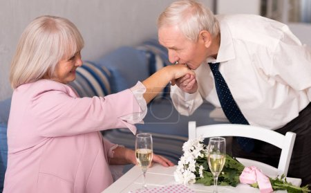 Attentive elderly man kissing his womans hand