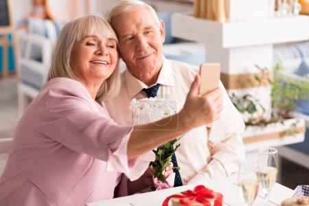 Adorable elderly love birds making a selfie