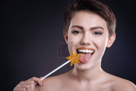 Cheerful woman eating lollipop