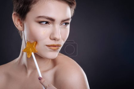 Attractive young woman holding lollipop