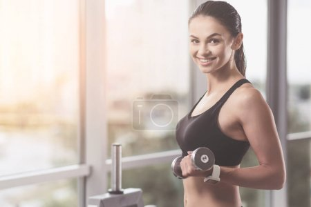 Smiling woman holding the dumbbells in gym