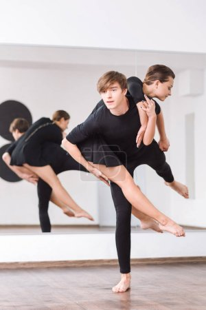 Photo for Constant practice. Good looking nice young man standing on one foot in front of the mirror and holding his female partner while visiting ballet dance class - Royalty Free Image