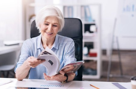 Smiling elderly businesswoman reading the magazine in the office
