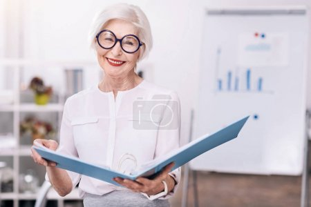 Photo pour Heureux de travailler dans cette entreprise. Heureuse heureuse heureuse femme debout devant le tableau blanc dans le bureau et la tenue du dossier document en souriant - image libre de droit