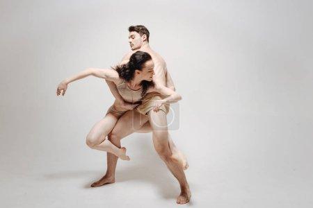 Photo pour Partenaires en danse. Danseurs créatifs doués inventifs debout dans le studio de couleur blanche et performer tout en démontrant leurs compétences - image libre de droit