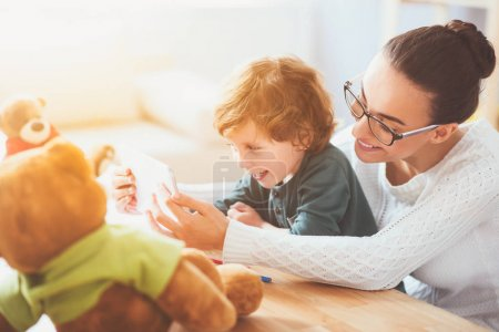 Young woman teaching her son and smiling