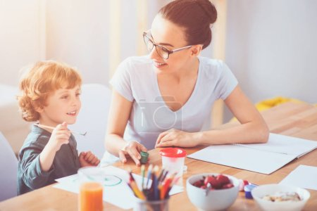 Delighted mother drawing with her toddler son together
