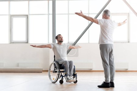 Handsome disabled man training in the gym with the orthopedist