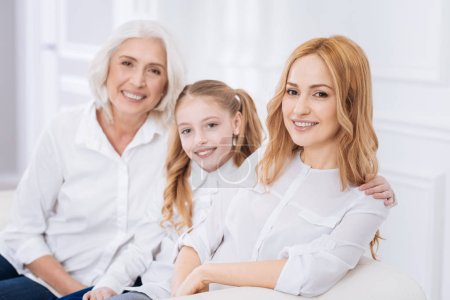 Photo for True emotions. Cheerful content adult woman smiling and sitting on the couch while resting with her daughter and senior mother - Royalty Free Image