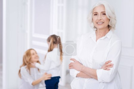 Deighted caring aged woman resting with her family at home
