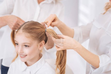 mother making ponytails for her little cute daughter