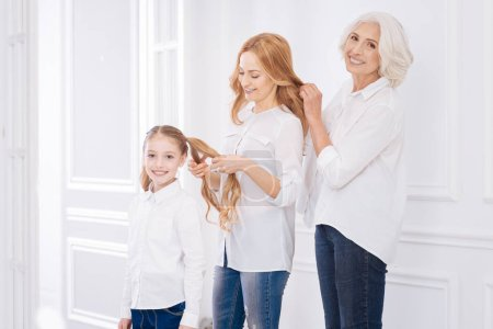 Positive family members making hairstyles for each other