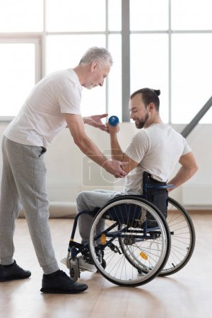 Confident disabled man exercising with his coach in the gym