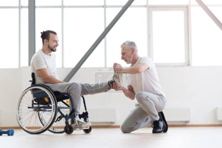 Aged orthopedist working with disabled patient in the gym