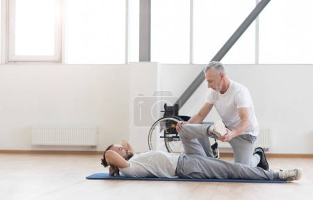 Proficient aged orthopedist working out with handicapped