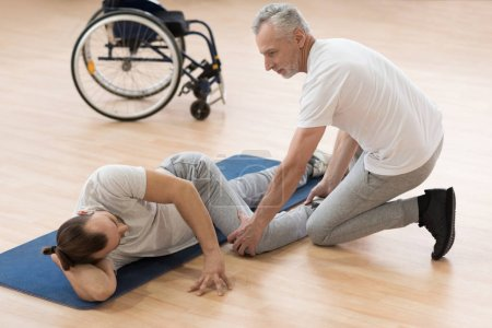 Outgoing physical therapist stretching the disabled patient in the gym