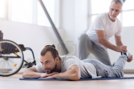 Aged bearded father stretching his disabled son in the gym