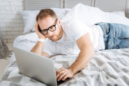 Pleasant bearded man using laptop at home