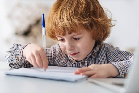 Focused diligent child writing an essay