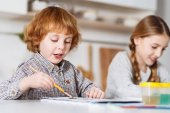 Passionate talented child drawing with his sister
