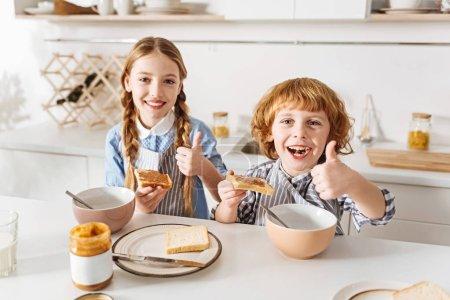 Charming energetic children loving their breakfast