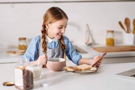 Photo for Scrolling down the page. Nice clever elegant child having a nutritious morning meal while using her gadget looking through some new articles - Royalty Free Image