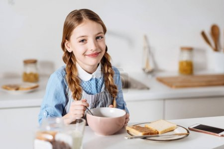 Beautiful girl looking delighted while eating breakfast