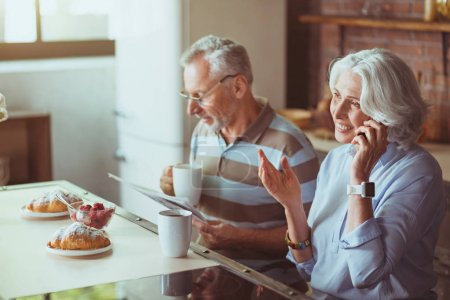 Positive aged couple having breakfast