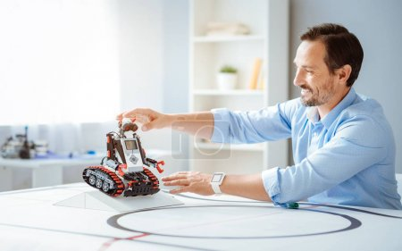Positive professional engineer testing robot