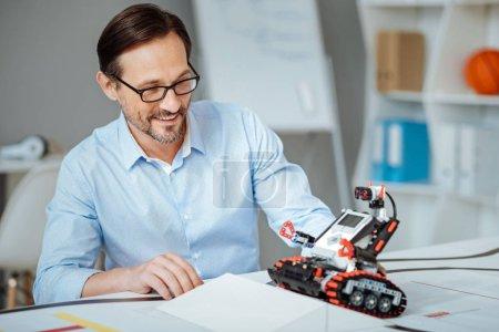 Joyful adult engineer testing the robot