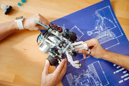 Photo for Match the scheme. Close up of robot in hands of professional engineers holding it and constructing together - Royalty Free Image