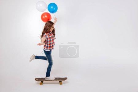 Amused child skateboarding in the studio