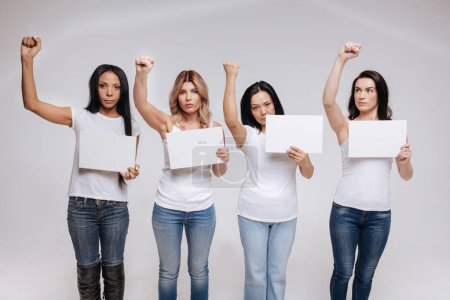 Photo for We change everything together. Wonderful modern passionate women standing united isolated on white background wearing similar clothes and striking a similar pose - Royalty Free Image