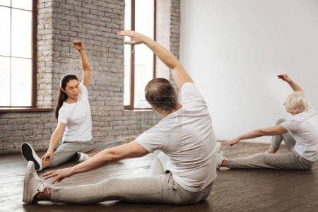 Group of three people stretching themselves