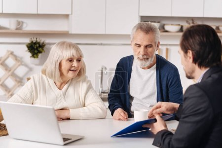 couple having conversation with realtor at home