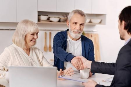 Photo pour Faire un marché. Sourire implique un couple âgé assis à la maison et conclure un accord avec un agent immobilier tout en exprimant sa positivité et en se serrant la main - image libre de droit