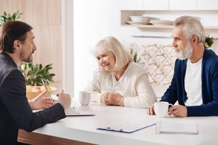 agent meeting with elderly couple of clients