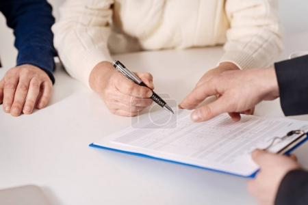 Photo pour Signature d'un prêt hypothécaire. Couple âgé résolu attentif assis à la maison et ayant une conversation avec l'agent immobilier lors de la signature du document - image libre de droit