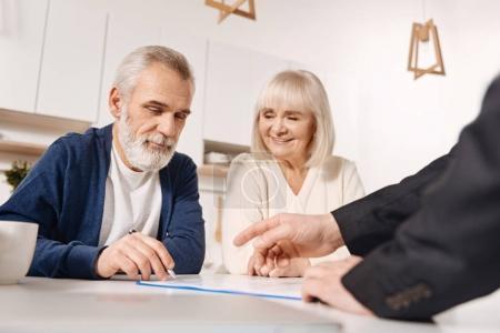 Photo pour Notre achat important. Couple de personnes âgées heureux et décidés assis à la maison et ayant une réunion avec un conseiller financier tout en signant l'accord - image libre de droit