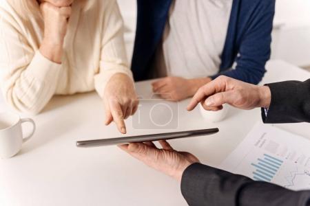 Photo pour Gadgets modernes utiles dans nos mains. Expérimenté agent immobilier qualifié mature travaillant avec un couple de clients âgés tout en exprimant des soins et en utilisant une tablette - image libre de droit
