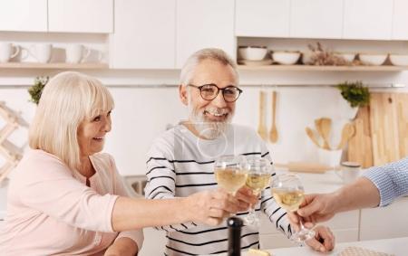 Photo pour On fête notre anniversaire. Mignon heureux couple retraité heureux dîner et célébrer leur anniversaire de mariage en famille tout en levant des verres pleins de champagne - image libre de droit