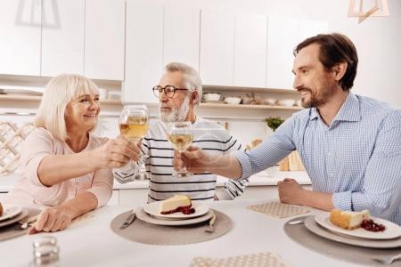 Photo pour Avec mes meilleurs vœux à mes parents. homme mûr heureux positif dîner et profiter des vacances avec ses parents âgés tout en levant des verres pleins de champagne et souriant - image libre de droit