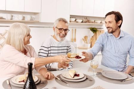 Smiling man enjoying family dinner at home