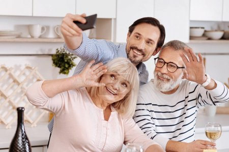 Smiling man taking selfie with senior parents