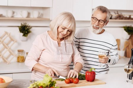 Photo pour Cuisiner un dîner en famille ensemble. Souriant charmant couple âgé debout dans la cuisine et cuisiner le dîner tout en exprimant le bonheur et les soins - image libre de droit