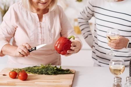 Amused elderly couple cooking dinner together