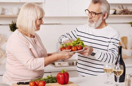 Photo pour Diriger une alimentation saine. Heureux couple âgé prudent debout dans la cuisine et cuisiner un dîner sain tout en exprimant le soin et l'amour - image libre de droit