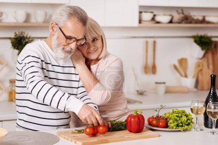 Photo pour Pour toujours t'aimer. Délicieux harmonique beau couple âgé debout dans la cuisine et cuisiner sain dîner tout en exprimant l'amour et câlin - image libre de droit