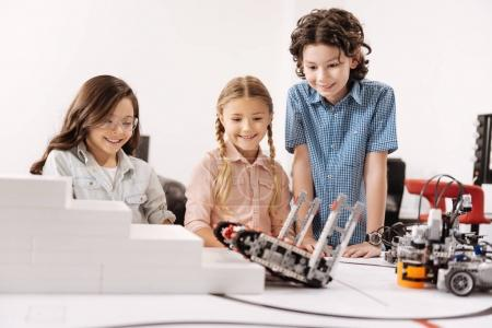 Delighted kids testing cyber robots