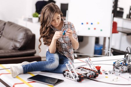 Smart little girl repairing electronic toy